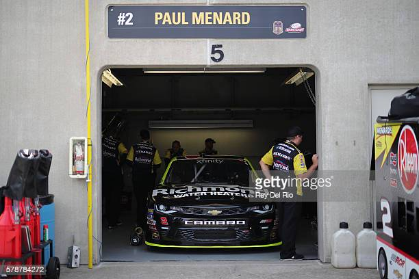 Crew members work on the car of Paul Menard driver of the Richmond/Menards Chevrolet in the garage area during practice for the NASCAR XFINITY Series...