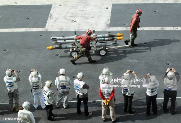 Crew members work on the flight deck of the nuclearpowered aircraft carrier USS George Washington in the South China Sea 150 miles away from Hong Kong