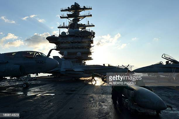 Crew members work on the flight deck of the USS Nimitz aircraft carrier in the Mediterranean Sea on October 25 2013 The US aircraft carrier which had...