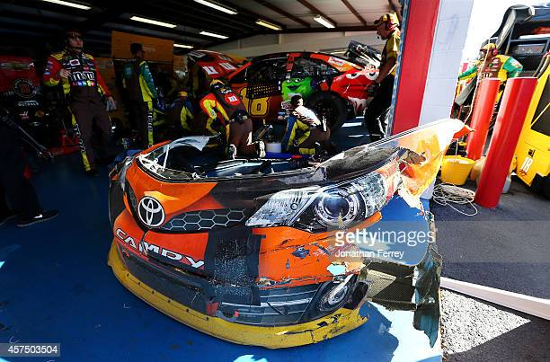 Crew members work on the MM's Halloween Toyota during the NASCAR Sprint Cup Series GEICO 500 at Talladega Superspeedway on October 19 2014 in...