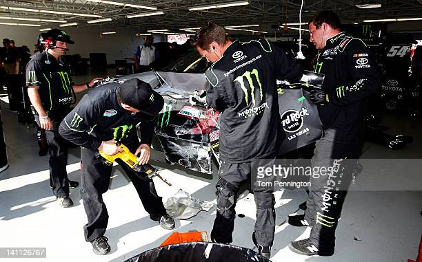Crew members work on the wrecked Monster Energy Toyota in the garage after an incident in the NASCAR Nationwide Series Sam's Town 300 at Las Vegas...