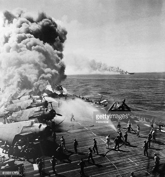 Crew members work to put out a blaze started aboard the USS Belleau Wood following a kamikaze attack. In the background, smoke pours from another...