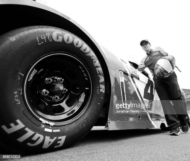 Crew memebrs push the car of Jimmie Johnson driver of the Lowe's Chevrolet through the technical inspection line before the Monster Energy NASCAR Cup...