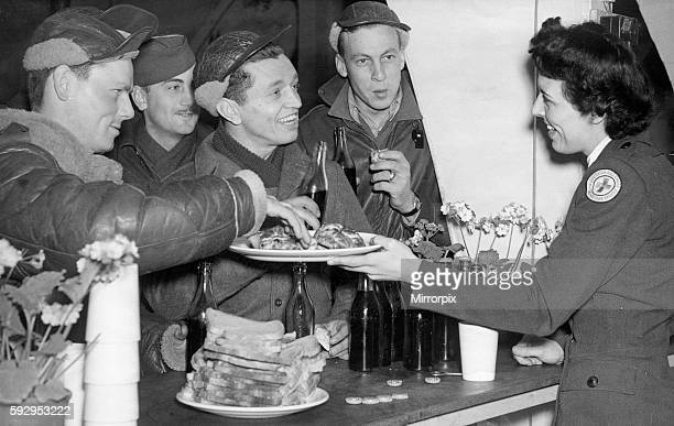 Crew men of the American B17 bomber Flying Fortress welcomed home by a Red Cross girl serving food in the mess of their base in England after...