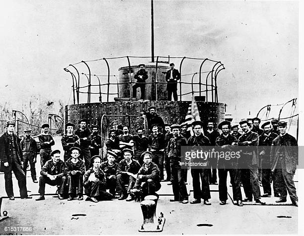 Crew of a monitor on the James River Crew posed on deck two black sailors in naval uniform posed toward the back