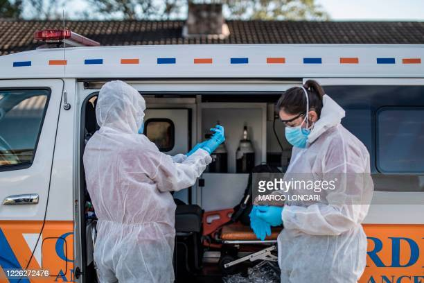 Crew of a private ambulance service in Port Elizabeth wear personal protective equipment , on July 11, 2020 ahead of checking on a patient affected...
