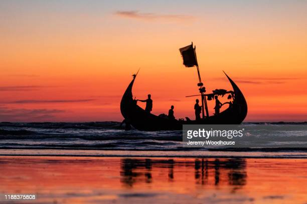 a crew of a traditional crescent boat awaits the high tide to lift them of the beach - bangladesh stock pictures, royalty-free photos & images