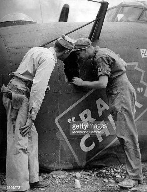Crew of an air base checking for damages a Liberator B24 returned from a mission Italy August 1944