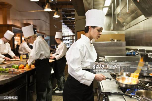 a crew of chef's working in a commercial kitchen, with a black chef in the foreground sauteing vegetables. - chef stock pictures, royalty-free photos & images