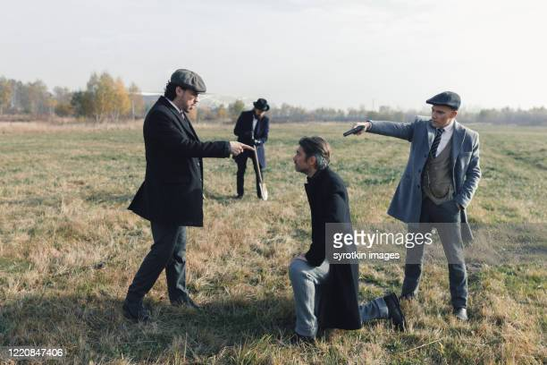 crew of gangsters pointing at head of prisoner. - dead gangster stock pictures, royalty-free photos & images