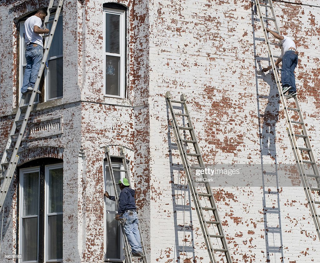 A crew of house painters prepares a townhouse on the corner of 5th and D Streets SE for a new coat of paint on Tuesday, May 6, 2008.