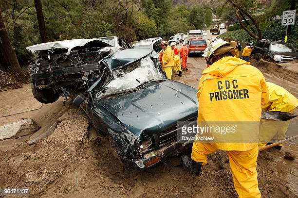 A crew of inmate firefighters from Azusa California digs out cars that were swept away as debris flows damaged homes on February 6 2010 in La Canada...