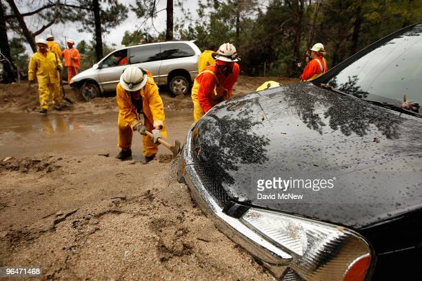 A crew of inmate firefighters from Azusa California digs out cars that were swept away as debris flows damaged homes after heavy rains caused...