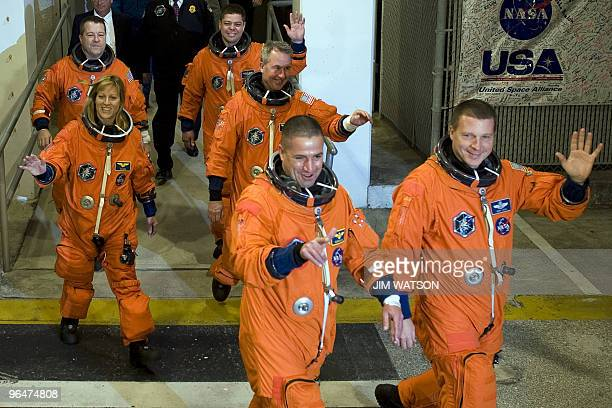 Crew of the space shuttle Endeavour STS130 wave as they walk out to the astrovan at Kennedy Space Center in Florida on February 7 2010 in advance of...
