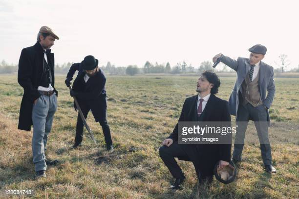 crew of thugs killing man. - dead gangster stock pictures, royalty-free photos & images
