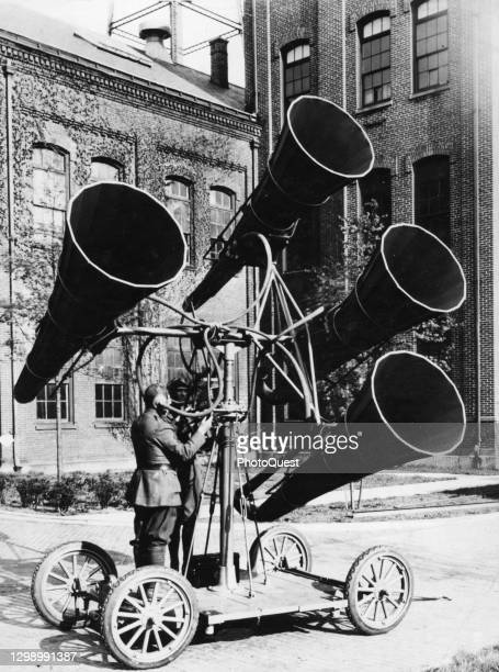 Crew of two soldiers operate an acoustic listening device, listening for the engine noise of approaching airplanes through the large horns mounted on...