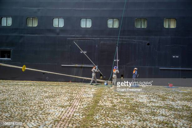 Crew paint and clean the hull of a cruise ship whilst passengers disembark in the port of Uturoa on the Island of Ra'iatea, French Polynesia.