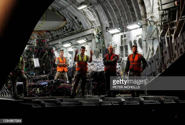 Crew prepares to remove cargo from a British Royal Air Force Boeing C-17A Globemaster III aircraft after landing at Brize Norton station, southern...