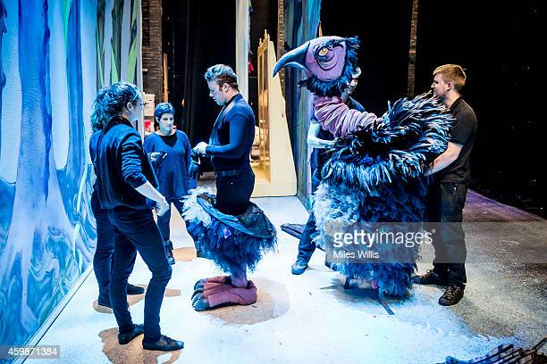 Crew put a costume on a performer behind the scenes during a performance of Mother Goose at Hackney Empire on December 2 2014 in London England
