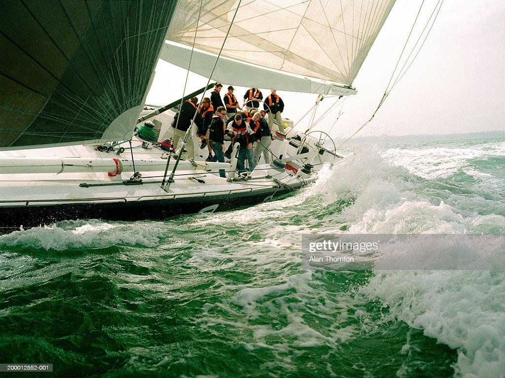 Crew sailing yacht through rough sea : Stock Photo