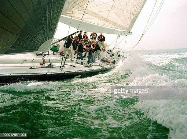 crew sailing yacht through rough sea - sailor stock pictures, royalty-free photos & images
