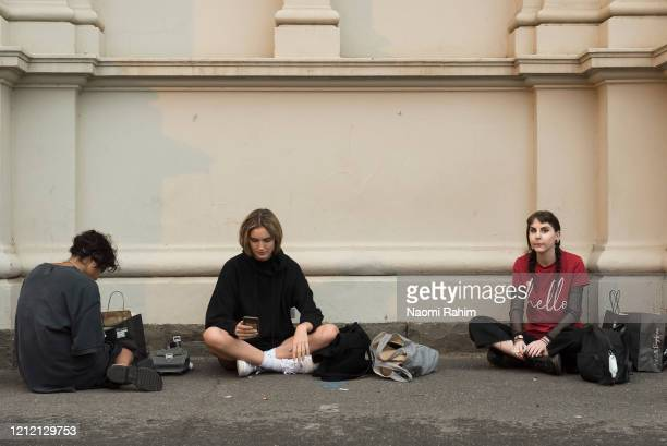 Crew sit outside the Royal Exhibition Building upon hearing the cancellation of the fashion show on March 13 2020 in Melbourne Australia Melbourne...