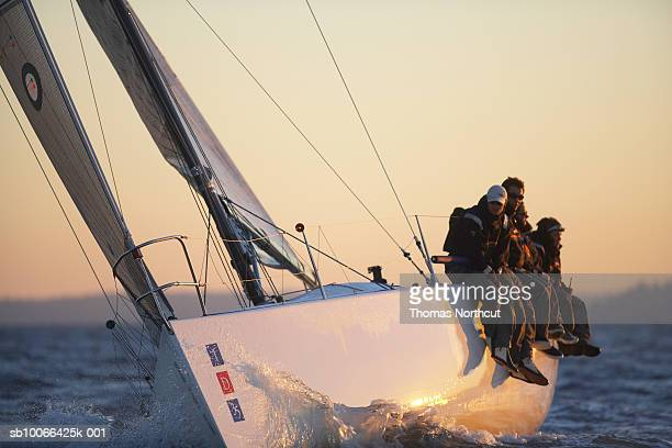 Crew sitting at edge of yacht