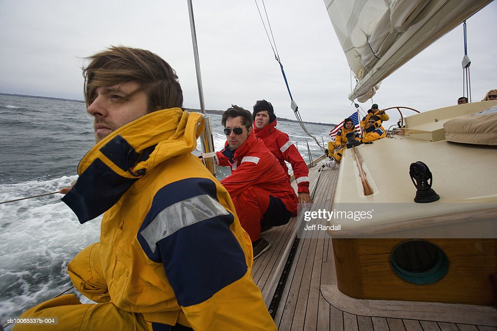Crew sitting on side of racing yacht : Foto stock