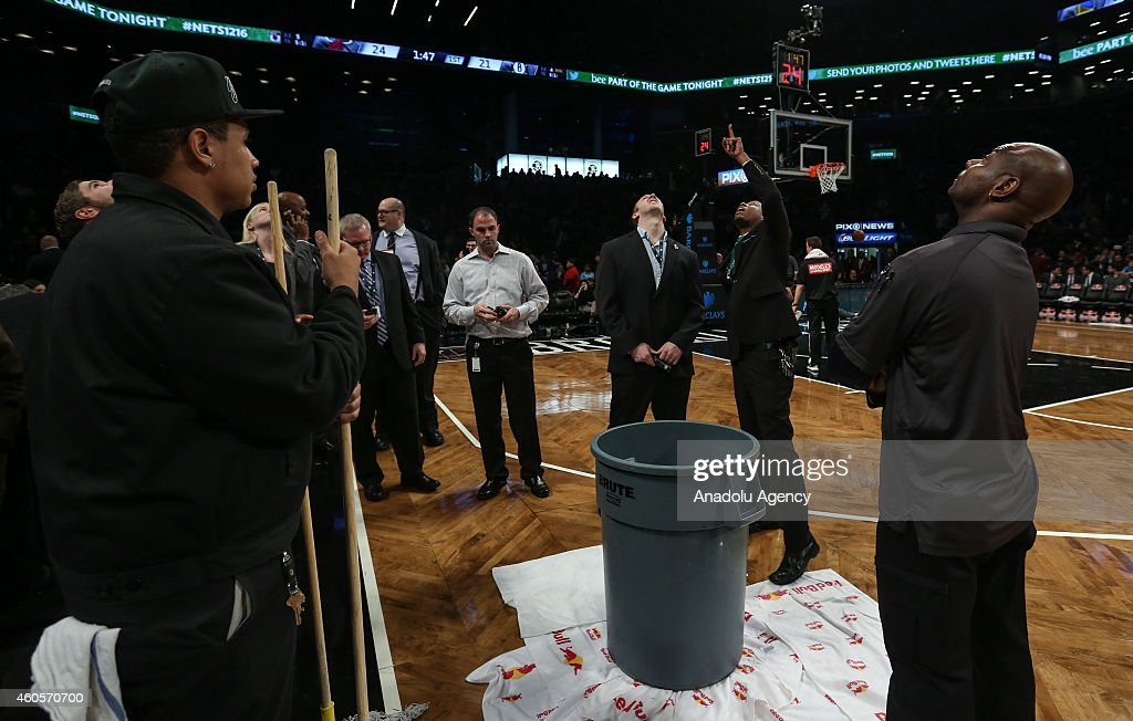 A crew try to clean up a leak in a delay in the first quarter during a game between the Brooklyn Nets and Miami Heat at the Barclays Center in the Brooklyn Borough of New York City on December 16, 2014.