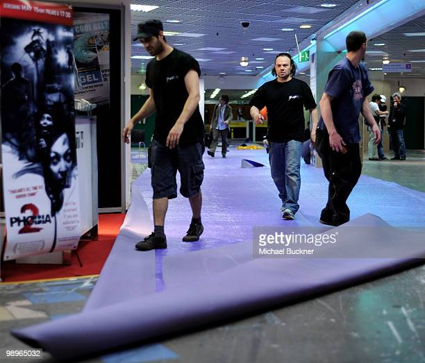 Crew workers install carpet in the Marche Du Film inside the Palais des Festivals prior to the annual film festival on May 11 2010 in Cannes France...