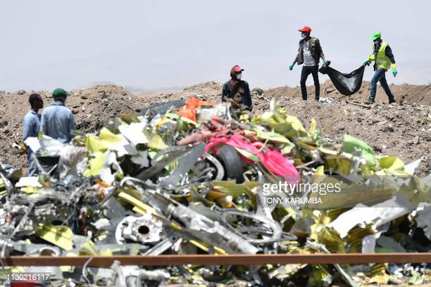 A crew working with an investigative team to clear the site after the Sunday crash of the Ethiopian Airlines operated Boeing 737 MAX aircraft carry...