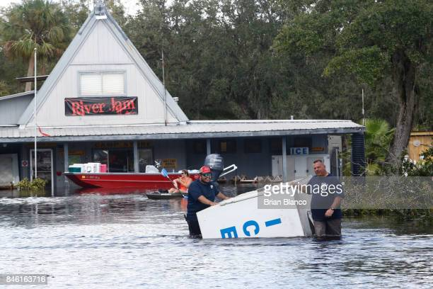 A crew works to salvage items including an ice machine as water from the nearby Peace River floods the Peace River Campground in the wake of...