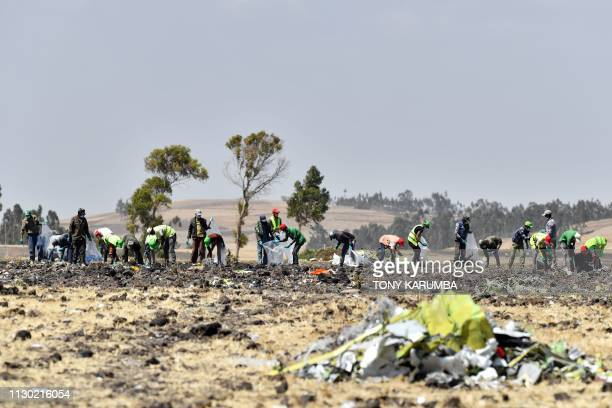 A crew works with an investigative team to clear the site after the Sunday crash of the Ethiopian Airlines operated Boeing 737 MAX aircraft at Hama...