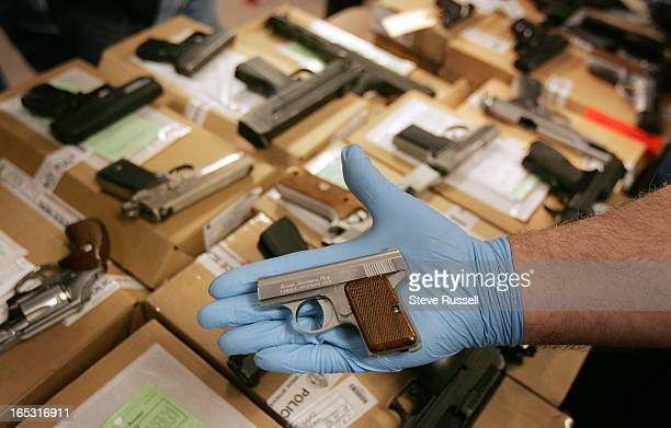 CREW05/19/06Detective Constable Mike Moore shows off the small Bauer 25 calibre that was among the some of the 30 firearms seized leading up to and...