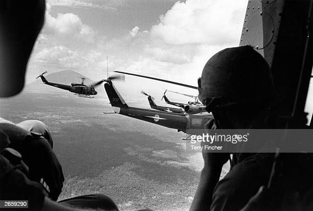 A crewman in a US helicopter watches a group of escorting Bell Huey helicopters during an operation in the Vietnam War