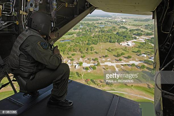 A crewman looks out the rear door of a US Air Force CV22 Osprey tiltrotor aircraft that combines the vertical takeoff hover and vertical landing...