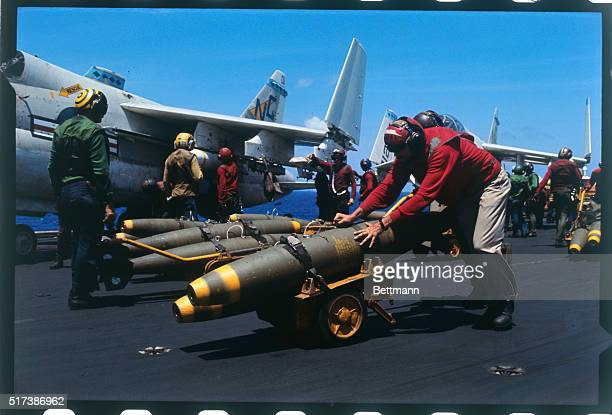 Crewman on aircraft carrier USS Constellation on duty on Yankee Station off Vietnam coast pushes cart with two 500lb bombs to be loaded on board Navy...