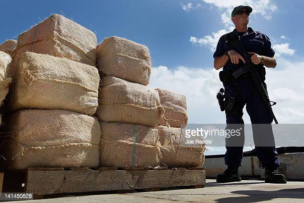 A crewmember from the Coast Guard Cutter Northland stands guard next to approximately 3500 pounds of cocaine confiscated from a 35foot gofast vessel...