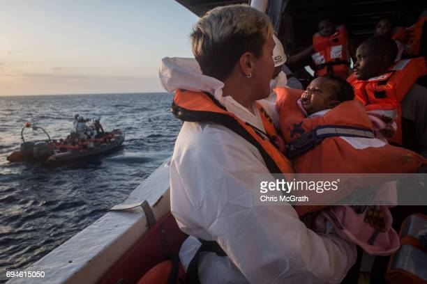 A crewmember from the Migrant Offshore Aid Station Phoenix vessel holds a child as they wait to transfer refugees and migrants to a waiting Italian...