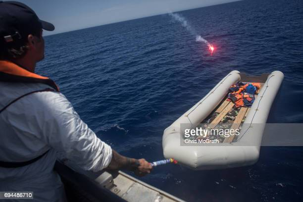 A crewmember from the Migrant Offshore Aid Station Phoenix vessel prepares to throw a flare into a small rubber boat to set it alight after all...
