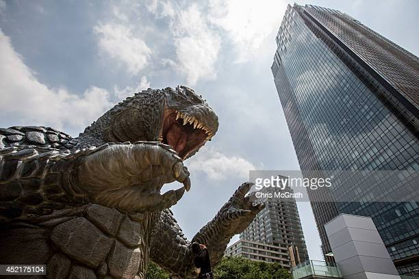 Crewmember Tetsuo Hayashi airbrushes the final touches to a 66 meter replica of the famous Godzilla at Tokyo Midtown on July 15 2014 in Tokyo Japan...