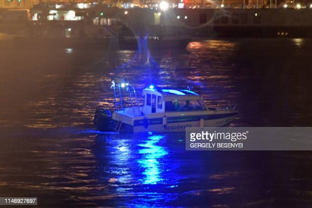 Crewmembers of a police boat search for survivors after the Hungarian 'Hableany' riverboat capsized after a collision on the Danube River in Budapest...