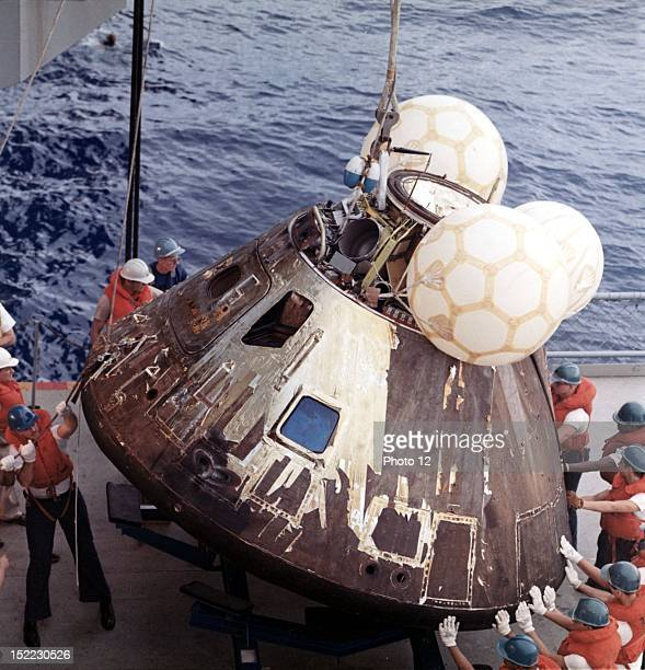 Crewmen aboard the USS Iwo Jima prime recovery ship for the Apollo 13 mission guide the Command Module atop a dolly on board the ship