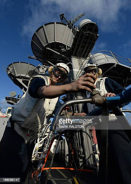 Crewmen from the aircraft carrier USS George Washington work on an 'Octopus' outlet for a desalination plant to provide drinking water as they begin...