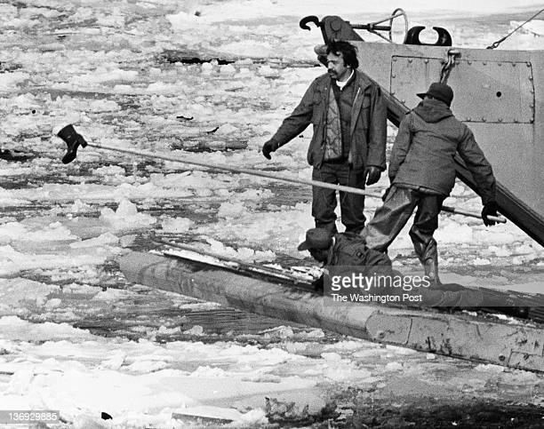 FILE Crewmen of a landing barge with the bow lowered fish a woman's boot from the Potomac River after the crash of Air Florida's Flight 90 in...