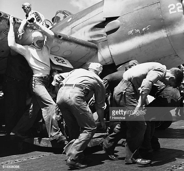 Crewmen on the USS Lexington pull a plane with a flat tire out of the way so that another plane can land November 1943 | Location USS Lexington