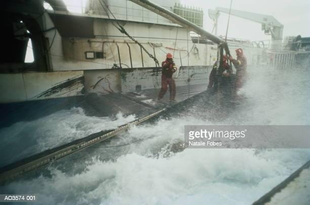 crewmen standing on deck of trawler during rough seas - storm stockfoto's en -beelden