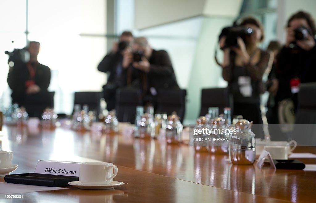 TV crews and press photographers record the empty chair with the name tag of German Education minister Annette Schavan prior to the weekly cabinet meeting lead by German Chancellor Angela Merkel at the Chancellery in Berlin on February 6, 2013. Germany's education minister and a close ally of Chancellor Angela Merkel was fighting for her political life Wednesday after having her doctorate revoked for plagiarism.