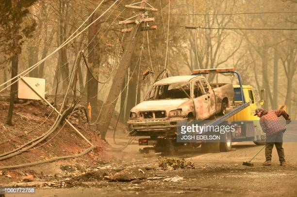 Crews begin removing abandoned vehicles from the streets after the Camp fire tore through the area in Paradise California on November 12 2018...