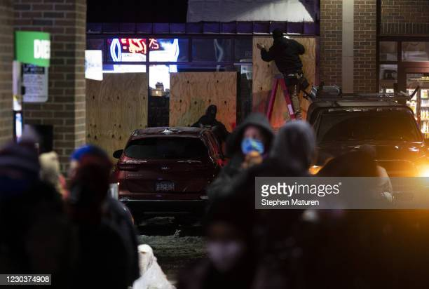 Crews board up a Holiday gas station during a vigil for Dolal Idd, who was shot and killed by Minneapolis Police last night, on December 31, 2020 in...